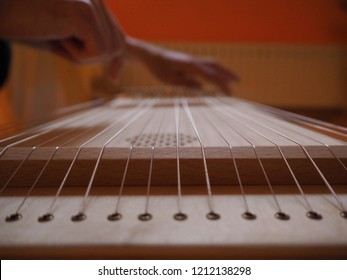 Sound healing therapy instrument Monochord, close up, with man hand playing on it.