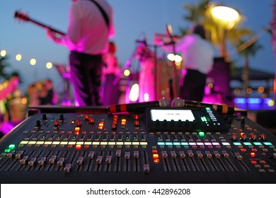Sound mixer and the musicians on the stage.Working sound panel on the background of the concert stage