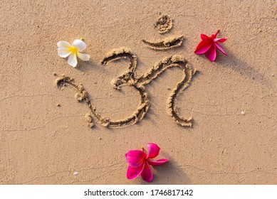 """The sound """"Om"""" or """"AUM"""" written in Sanskrit - in the Hindu and Vedic traditions - sacred sound, the original mantra. Used in yoga practices and meditation techniques. Frangipani flowers on the sand"""
