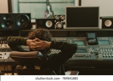sound producer relaxing in armchair at recording studio