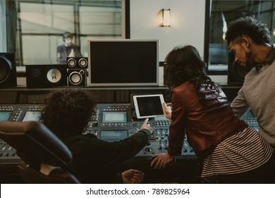 sound producers using tablet together at recording studio