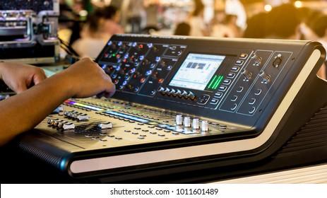 Sound technician control professional audio mixer in concert. Selective focus.