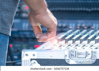Sound technician and lights technicians control the music show in concert.Professional audio, light mixer controller panel.Pro equipment for concerts.Stage lighting control.Hand adjusting audio mixer