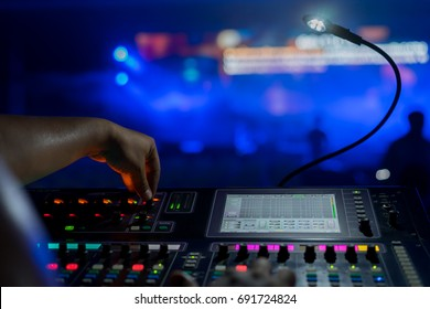 Sound technician and lights technicians control the music show in concert.Professional audio,light mixer controller panel.Pro equipment for concerts.Stage lighting control.Hand adjusting audio mixer