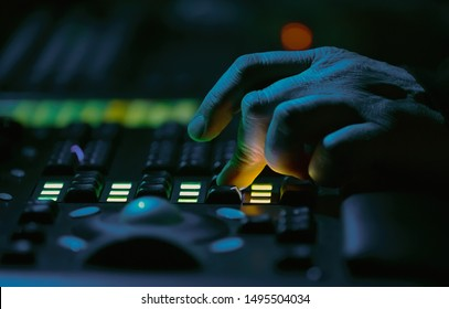 Sound technician works on audio mixer panel at rock concert in nightclub.Professional working on mixing controller at festival in music hall.Hand of specialist adjusting volume on party in the club