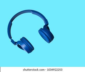 Sounds. Headphones. Earphones on blue background. Headphones for music sound. Isolated on blue background. Blue headphones on blue background.