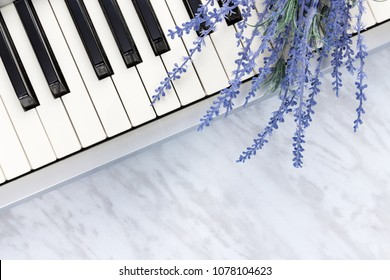 Sounds of nature. Blue lavender flowers on piano keys, on marble background.
