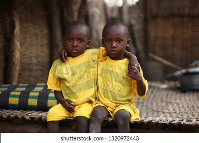 soungou rongou river, Senegal, Africa, May 26, 2017: close up horizontal photography of two boy twins in yellow shirts and shorts, outdoors on a sunny day with a hanmade palm fence  in the background