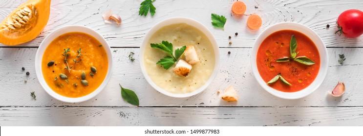 Soup Assortment. Set of various seasonal vegetable soups and organic ingredients, banner, copy space. Homemade colorful vegan vegetarian soups.