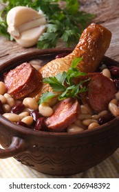 soup with beans, chicken legs and sausages in a bowl on the table. close up vertical
