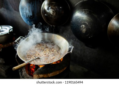 Soup boiling on large frying pan on rural stove and vapors of food smell in kitchen. Traditional rural asian life style, Rural kitchen using bio wood fuel for cooking.