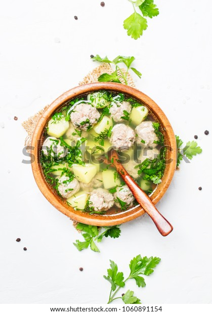 Soup with chicken meatballs, white background, top view