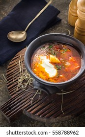 Soup in clay bowl on chopping board. Dark background,  Style rustic. Selective focus.