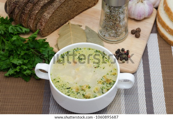Soup decorated with fresh vegetables and bread.