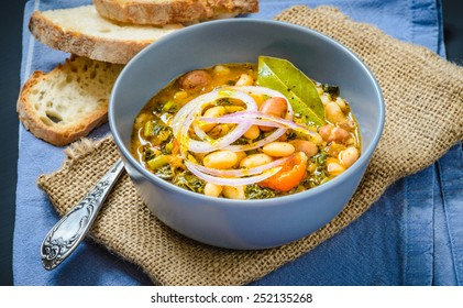 Soup with different vegetables, cannellini beans, cavolo nero, bread.Famous typical tuscan soup, ribollita. Plate with soup.