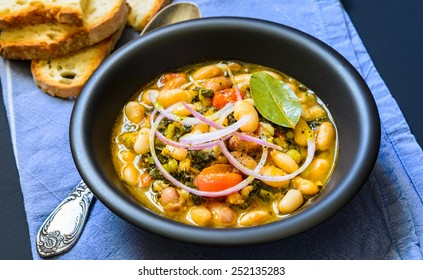Soup with different vegetables, cannellini beans, cavolo nero, bread.Famous typical tuscan soup, ribollita.Plate with soup.