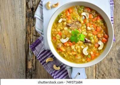 Soup with lentils, carrots, meat, vegetables and cashew nuts, in a plate, top view, on a white board, old wooden rustic background, copy space