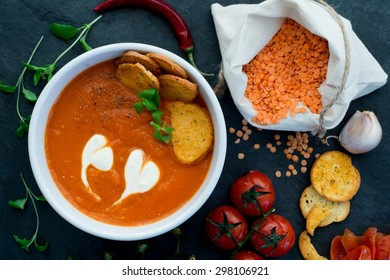 Soup made of baked cherry tomatoes and red lentil with fresh marjoram. Decorated with heart-shaped pattern made of cream and crispy croutons.