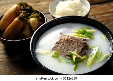 Soup made of Beef and Bone with Scallion on top and Steamed Rice and Spicy Radish in the background.