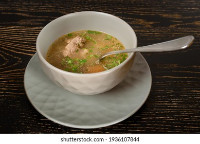 Soup with meat and herbs in a gray bowl on a dark wooden table. Chikhirtma Georgian dish.