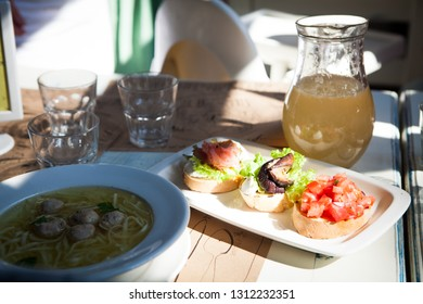 Soup with meatballs and three sandwiches snacks with a carafe with juice on the table during lunch