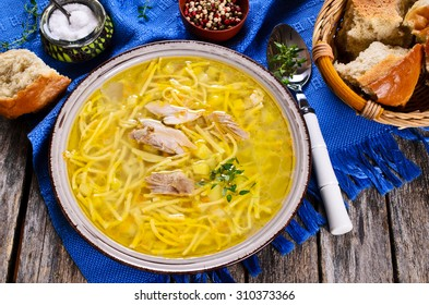 Soup with pasta, meat and vegetables in a ceramic bowl