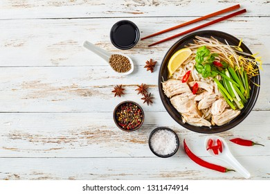 soup Pho Ga with chicken breast, rice noodles, bean sprouts, spices and fresh herbs in an earthenware bowl, vietnamese cuisine, view from above, flatlay, copy space
