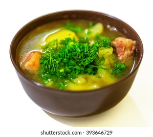Soup with pork and potato in bowl isolated on white background