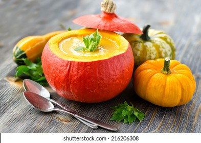 Soup in a pumpkin with different pumpkins for autumn dinner