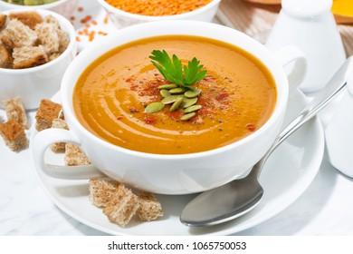soup of pumpkin and lentils in a bowl, closeup horizontal