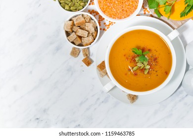 soup of pumpkin and lentils in a bowl on white background, top view closeup