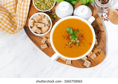 soup of pumpkin and lentils and ingredients on wooden board, top view horizontal