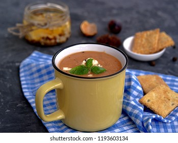 Soup puree from baked aubergines and tomatoes in a yellow mug. Served with feta cheese and crackers.