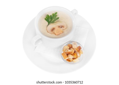 Soup puree, cream soup white, beige with mushrooms, championons and crackers, dry bread. On a napkin in a white plate isolated white. Serving dishes in a cafe, restaurant, for a menu. Side view