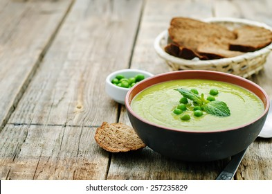 soup puree of green peas on a dark wood background. tinting. selective focus