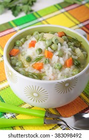 Soup with rice, green peas and carrots in a white bowl