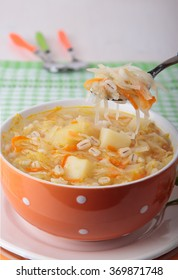 Soup of sauerkraut with pearl barley, potatoes in a bowl