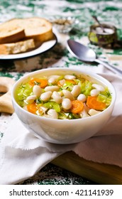 Soup with vegetables and beans in a dish. Selective focus.