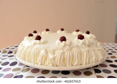 Sour cherry cake with whipped cream on a spotted tablecloth.