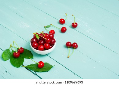 sour cherry fruits at bowl on old blue wood table