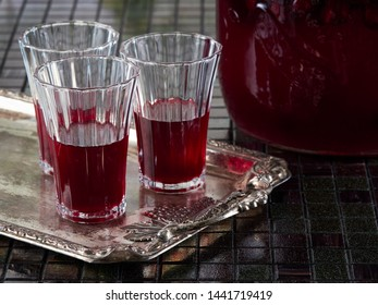 Sour cherry liqueur in crystal glasses and a jar of homemade sour cherry liqueur