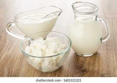 Sour cream in gravy boat, milk in jug, cottage cheese in transparent bowl on wooden table