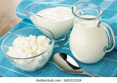 Sour cream in gravy boat, milk in jug, cottage cheese in transparent bowl, spoon on blue napkin on wooden table