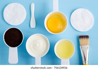 Sour cream (greek yogurt), raw egg, ground coffee and olive oil in a small scoops. Ingredients for preparing diy masks, scrubs, moisturizers. Homemade cosmetics. Top view, copy space.