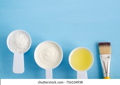 Sour cream (greek yogurt), shredded coconut and olive oil  in a small scoops. Ingredients for preparing diy masks, scrubs, moisturizers. Homemade cosmetics. Top view, copy space.
