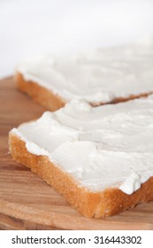 Sour cream on bread and lined up on a wooden board.
