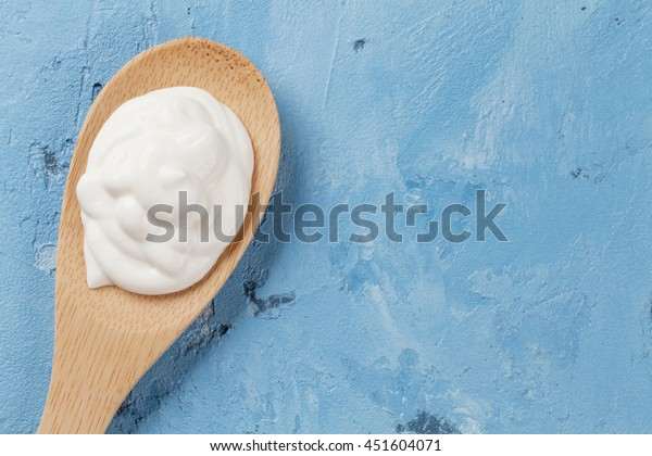 Sour cream on spoon. Dairy products on stone table. Top view with copy space