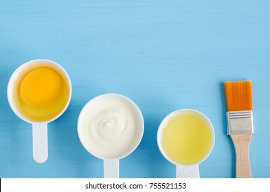 Sour cream (or greek yogurt), raw egg and olive oil in a small plastic scoops - ingredients for preparing diy masks, scrubs and moisturizers. Homemade cosmetics. Top view, copy space