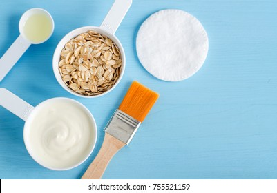 Sour cream (or greek yogurt), rolled oats and olive oil in a small plastic scoops - ingredients for preparing diy masks, scrubs and moisturizers. Homemade cosmetics. Top view, copy space.