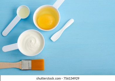 Sour cream (or greek yogurt), raw egg and olive oil in a small scoops. Ingredients for preparing diy masks, scrubs, moisturizers. Homemade cosmetics. Top view, copy space.